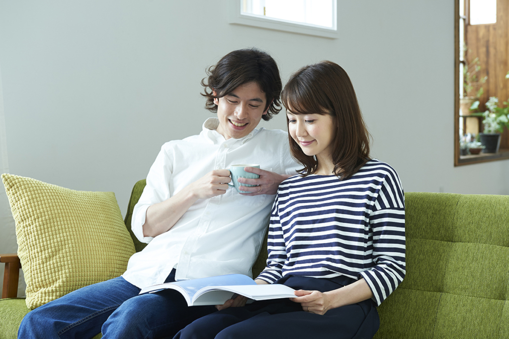夫婦でソファーに座り、カタログを見ている風景