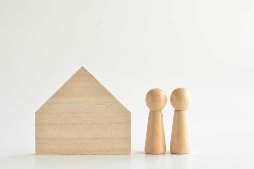 積み木で作った家と夫婦のイメージ
