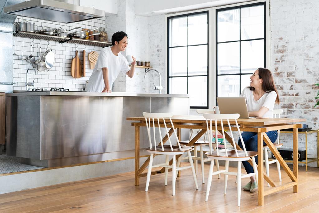 キッチンのカウンター越しに話す若い夫婦