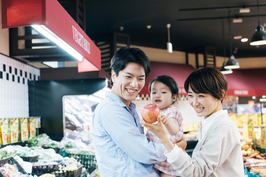 スーパーでリンゴを赤ちゃんに見せる若い夫婦