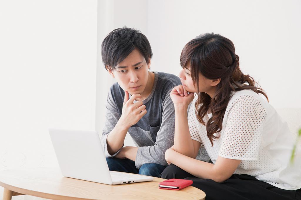 パソコンで依頼先を検討する夫婦